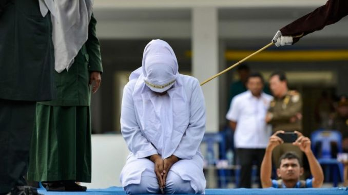 A woman is whipped in public by a member of the Sharia police in Banda Aceh on October 31, 2019