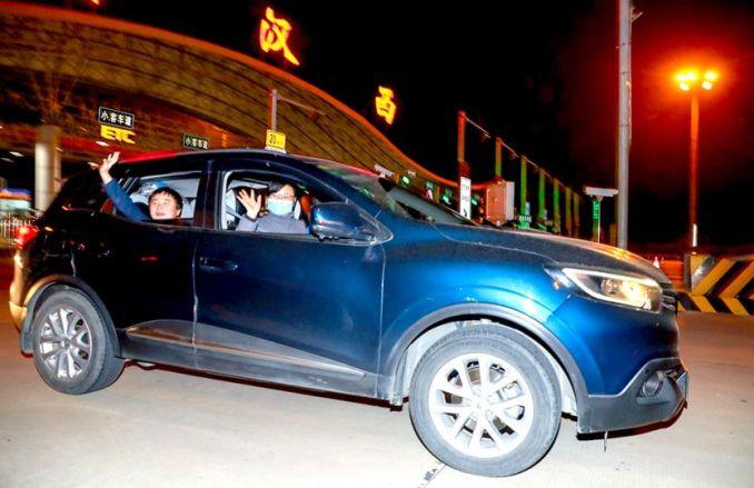 Des passagers saluent une voiture qui passe devant un poste de péage