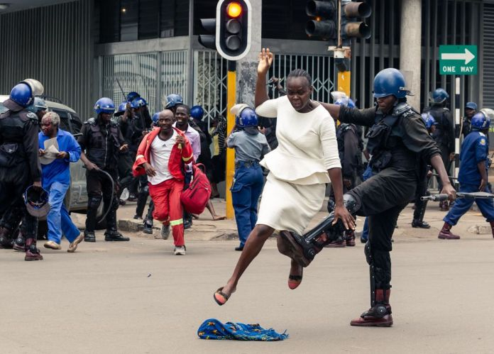 A riot police officer attacks a woman in Harare, Zimbabwe - Wednesday 20 November 2019