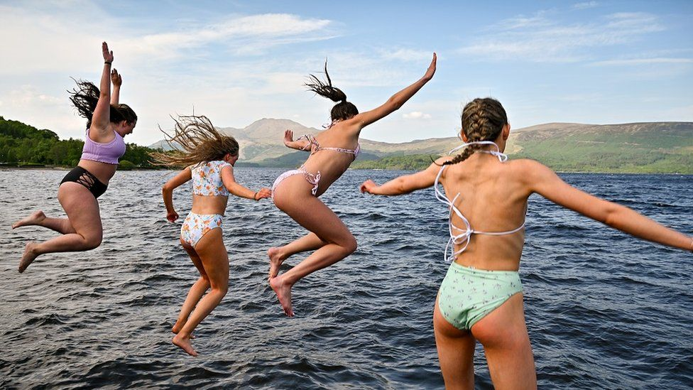 Four women jumping into a Scottish loch, 2 June