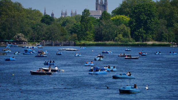 People ride pedalos on the Serpentine in Hyde Park, London, in view of the Palace of Westminster on Bank Holiday Monday