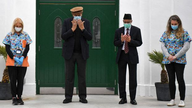 Health workers and faith leaders stand outside the Fazl mosque vaccination centre in southwest London and take part in a minutes silenceHealth workers and faith leaders at the Fazl mosque vaccination centre in southwest London take part in the minute's silence