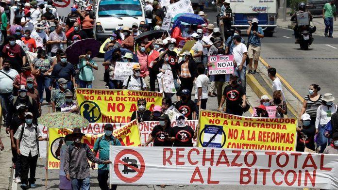Protestors with signs in San Salvador