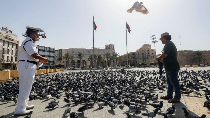 Libyan men feed pigeons in an empty Martyrs Square in downtown Tripoli, Libya - Saturday 7 August 2021