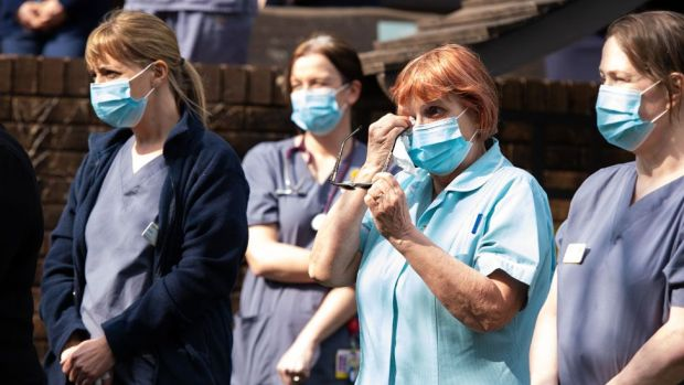 Staff observe a minute's silence outside a Marie Curie hospice