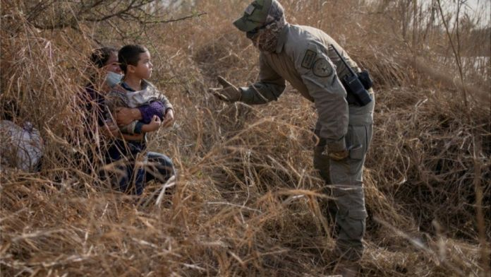Migrants crossing into the US are stopped by an official in Texas