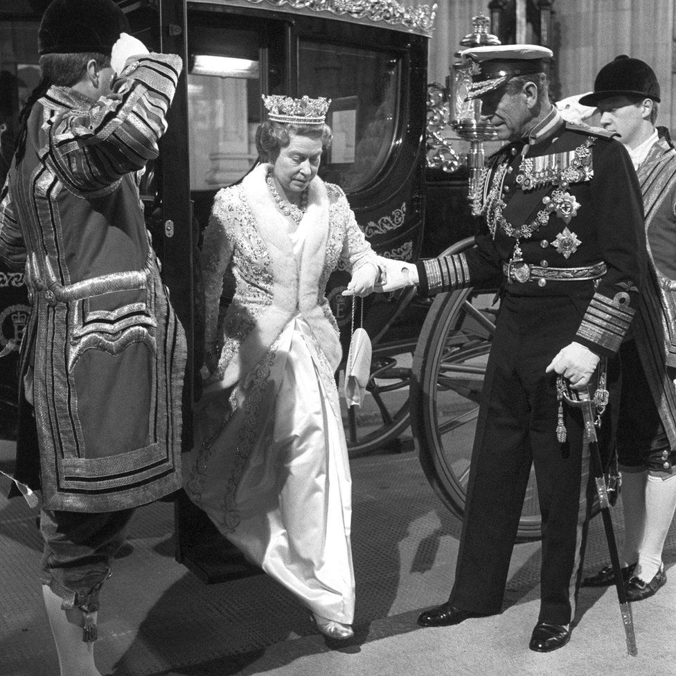 The Duke of Edinburgh helping Queen Elizabeth II to alight from the new £120,000 Australia State Coach, Australia's bicentennial gift, at the Houses of Parliament as they arrive for the State Opening