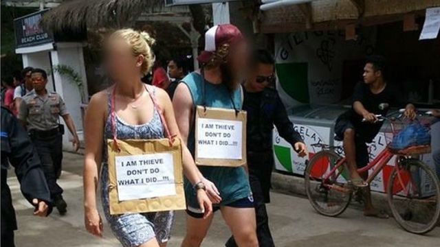 The two foreigners, walking down a small street with signs around their necks.