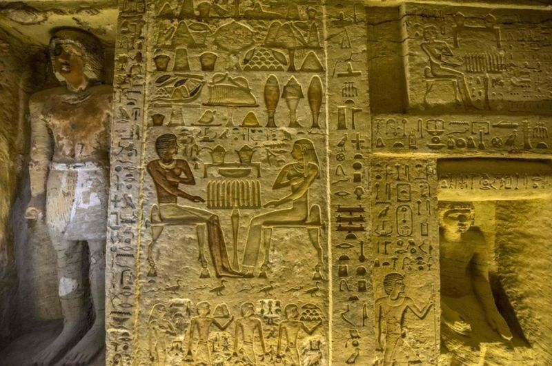 A wall covered in engraved hieroglyphs, including people, weighing scales, birds and what appears to be food