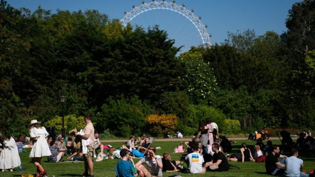 Members of the public enjoy the sun in St James Park on Sunday