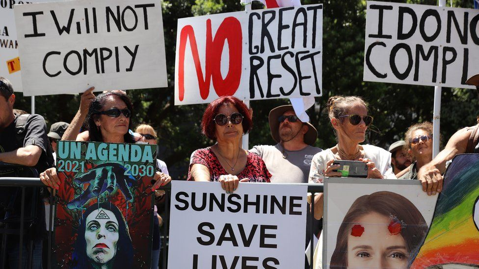 """People hold placards protesting the United Nations and the """"great reset"""" at a rally of conspiracy theorists and supporters of US President Donald Trump on January 14, 2021 in Wellington, New Zealand"""