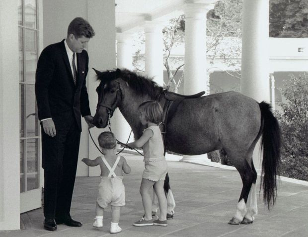President Kennedy is seen with his daughter Caroline, son John and pet pony Macaroni