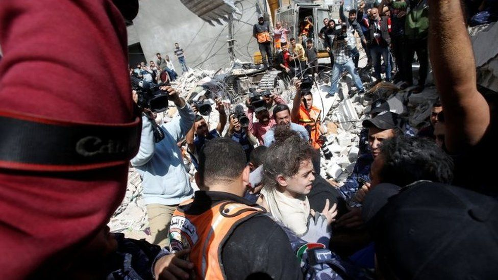 Rescuers carry Suzy Eshkuntana, 6, as they pull her from the rubble of a building at the site of Israeli air strikes