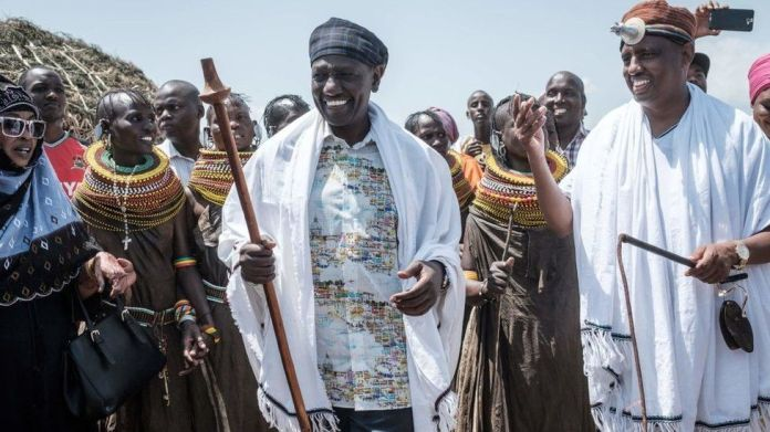 Kenya's vice-President William Ruto (C) and Marsabit County Governor Mohammed Muhamud Ali (R) walk with performers of the Turkana tribe during the 11th Marsabit Lake Turkana Culture Festival in Loiyangalani near Lake Turkana, northern Kenya, on June 28, 2018