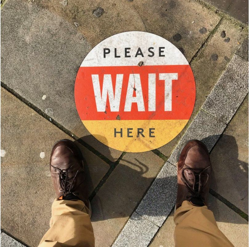 A sign on the ground instructing people to wait