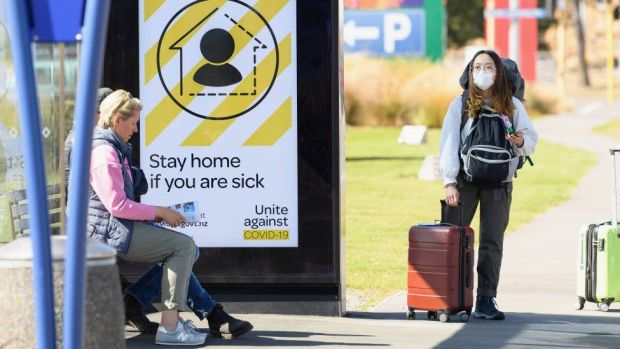 A traveller wearing a protective mask is seen waiting for a bus near Christchurch International Airport