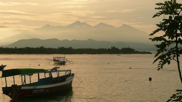 Photo taken on 1 May 2011 shows the sun rising over the Gili Islands, with the mountains of Lombok in the background.