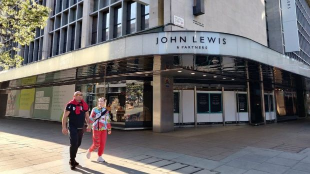 Two people walk past John Lewis on Oxford Street