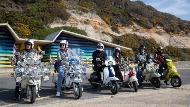 Members of a local scooter club on the seafront on Boscombe beach