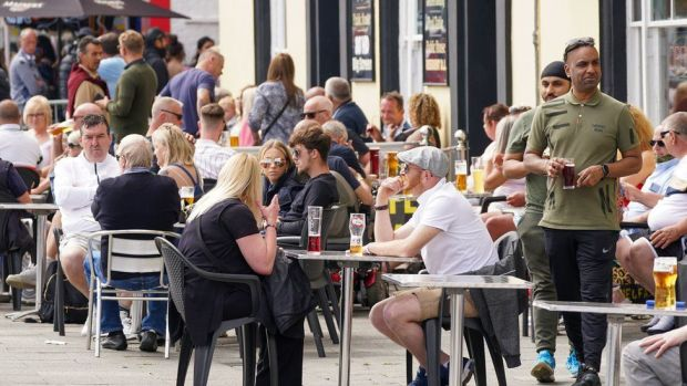 People enjoy a drink at a pub along the seafront in Southend on Sunday