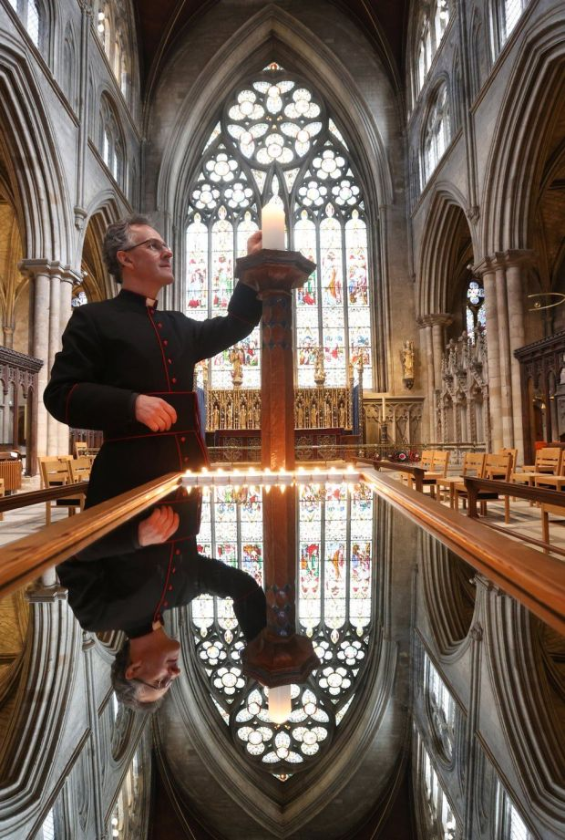 The Dean of Ripon lights a large candle in a cathedral