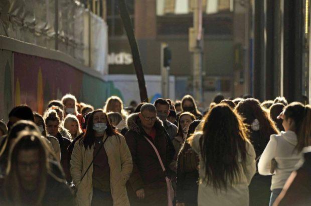 Dozens of shoppers walk along a street in Belfast