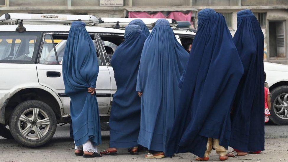 Mulheres vestindo uma burca esperam para embarcar em um táxi local em Cabul em 31 de julho de 2021