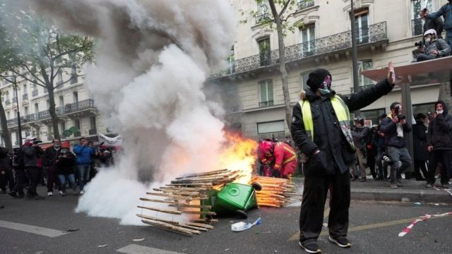 """A """"Yellow vest"""" protester gestures near a fire during the traditional May Day protests in France"""