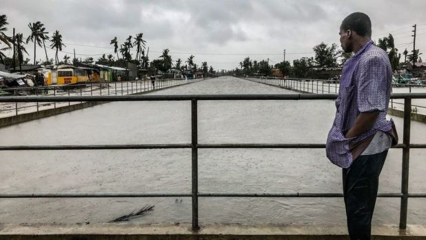 A man stands on a bridge overlooking a flooded river