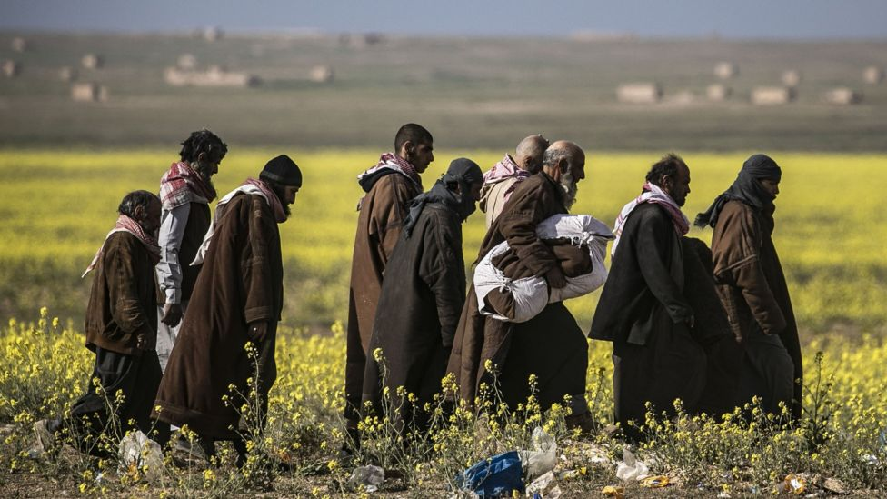 Suspected militants evacuated from the last IS-held village of Baghuz walk towards a screening area (6 March 2019)