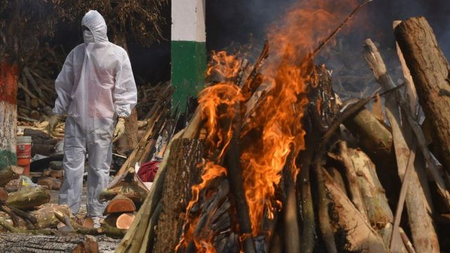 A Family member, wearing a Personal Protective Equipment (PPE), performs the last rites for COVID-19 victims at a cremation ground in New Delhi, India, 29 April 2021.