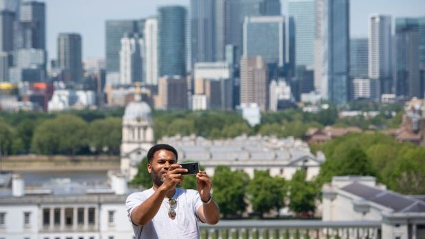 A man takes a selfie with the skyline of Canary Wharf, from the Royal Observatory in Greenwich Park, London
