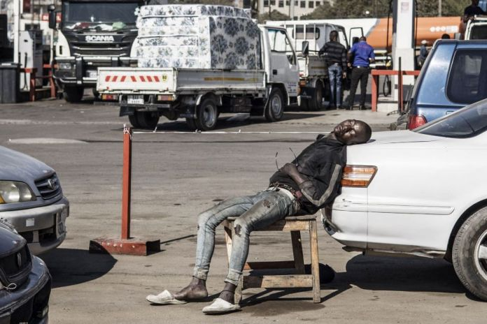 A car wash attendant asleep on a chair with his head resting on a vehicle, Lusaka, Zambia - Tuesday 10 August 2021
