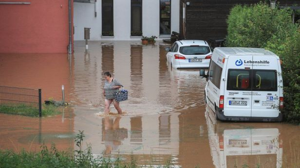 A woman wades across floodwater as she goes out shopping following heavy rainfall