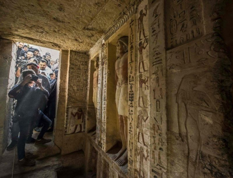 Journalists enter a newly-discovered tomb at the Saqqara necropolis, 30 kilometres south of the Egyptian capital Cairo