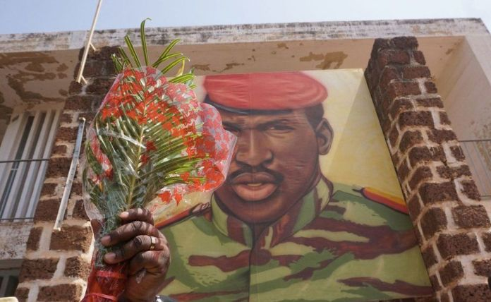 A man holds flowers next to an image of Thomas Sankara, in front of the headquarters of the National Council of the Revolution (CNR), in Ouagadougou in 2019. The former leader was killed at the site in 1987.