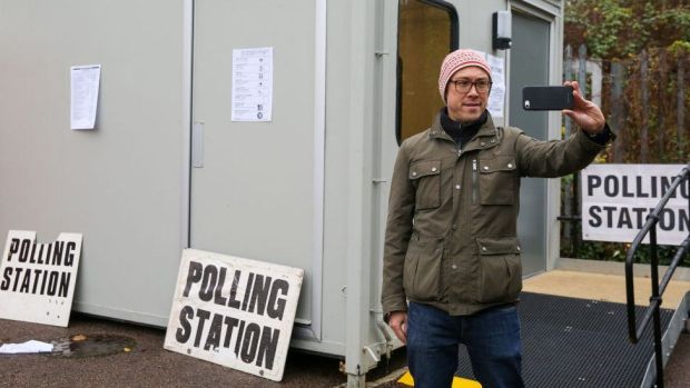 Man taking a selfie outside a polling station