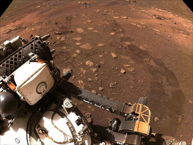 An image of part of the rover and its tracks on the ground, taken during Perseverance's first drive on 4 March 2021