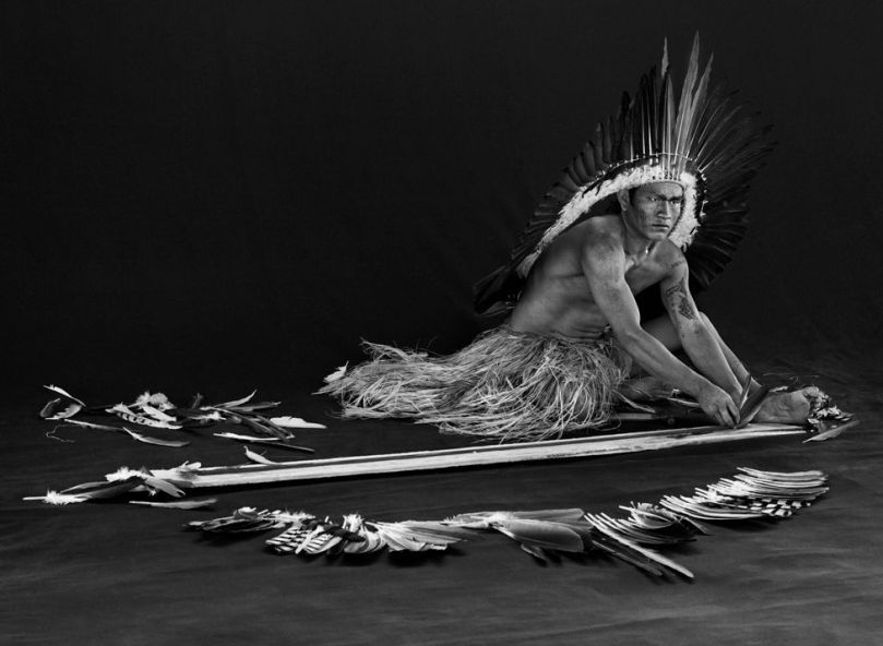 Black and white photograph of a man making feather adornments