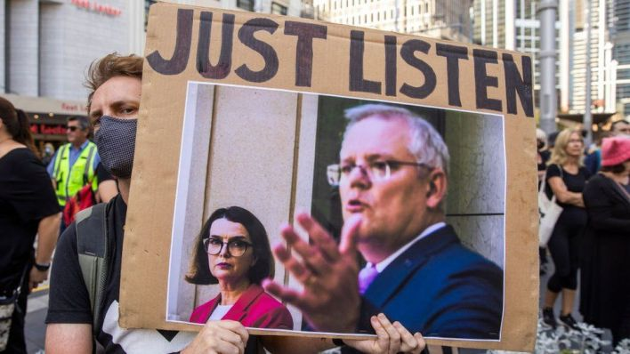 A protester holds up a sign urging Prime Minister Scott Morrison to listen to women's accounts
