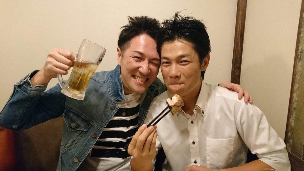 Yuichi Ishii levanta um copo de cerveja abraçado a um amigo