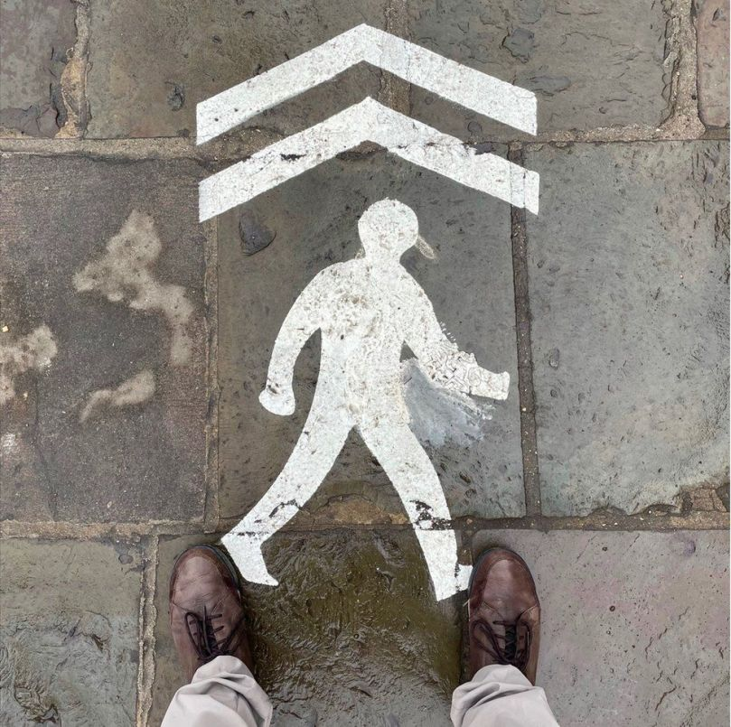 A stencil outline of a walking figure with an arrow