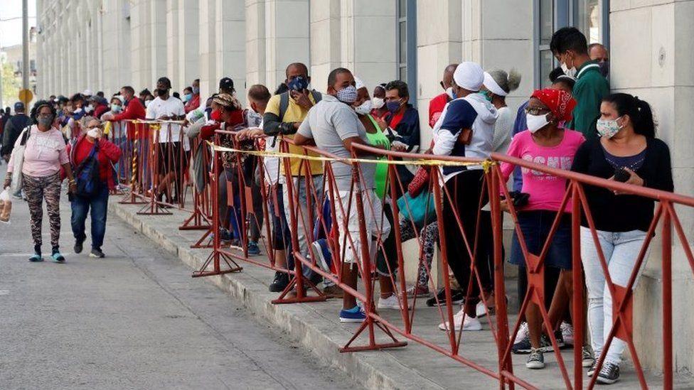 People wearing masks line up to buy food in a market in Havana, Cuba, 02 February 2021.