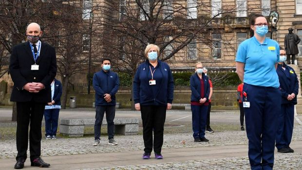 Health workers stand outside the Glasgow Royal Infirmary and observe a minute's silence