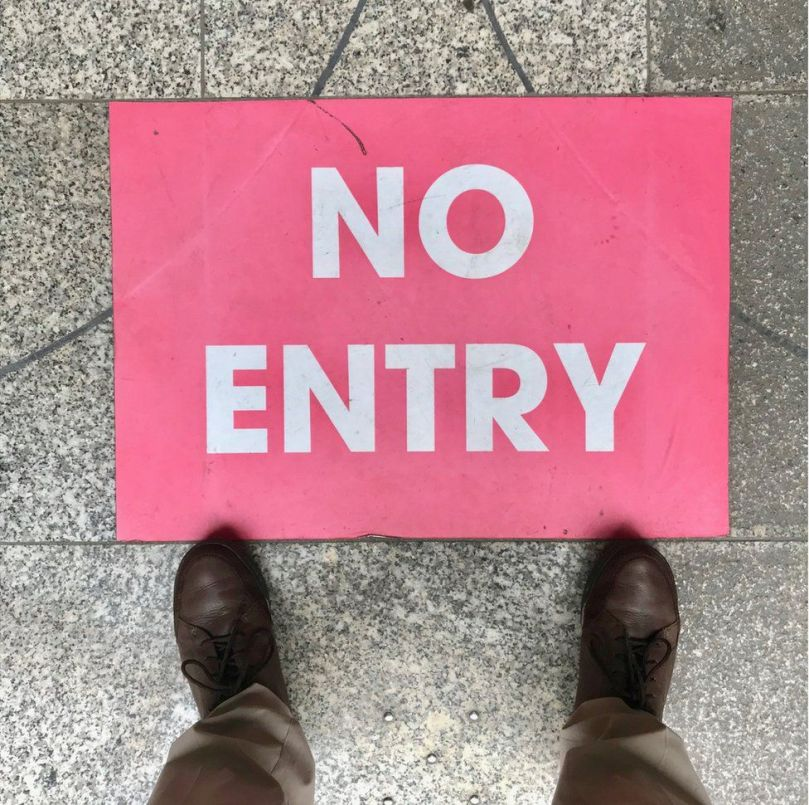 A pink sign on the ground that says 'No Entry'