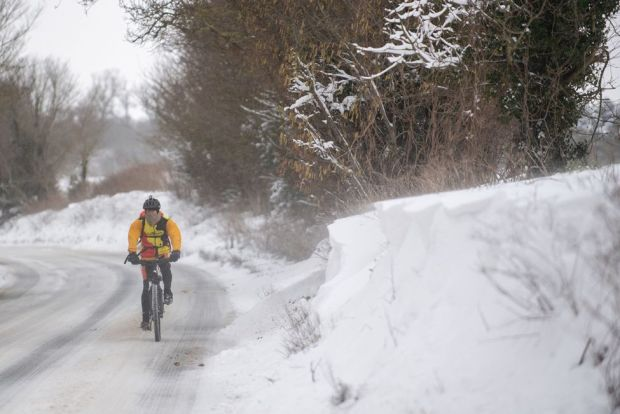 A cyclist makes their way through snow in Barham, near Ipswich, on 8 February 2021