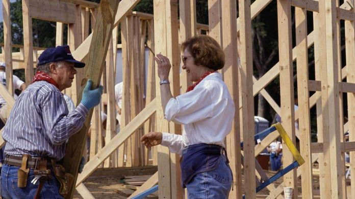 Jimmy Carter and wife Rosalynn Carter help build a house for Habitat for Humanity, 1992