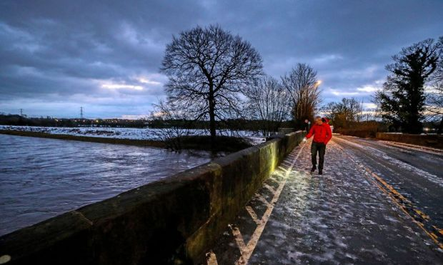A council worker in Didsbury, Manchester, checks a bridge for damage after heavy rainfall, on 21 January 2021