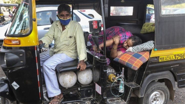 A woman lies in a rickshaw waiting for for medical assistance