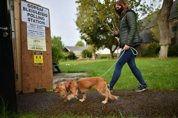 A dog and its owner walk into a polling station in Cardiff, Wales